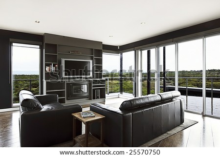 A modern luxury home interior living area with couch and flat screen TV and a beautiful view. - stock photo