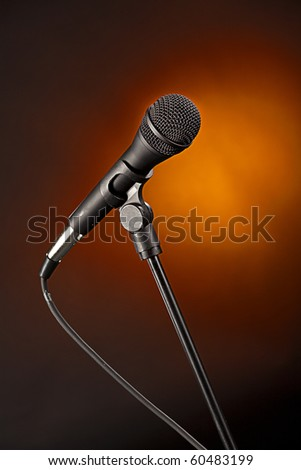 A modern microphone isolated against a spotlight gold background in the vertical format. - stock photo