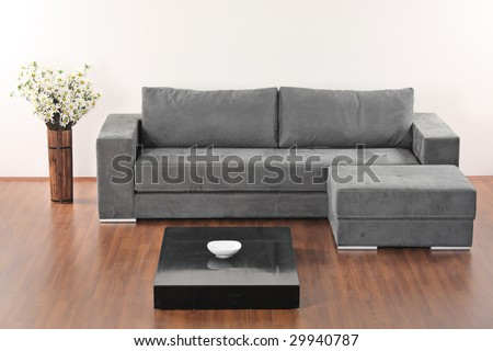 A modern minimalist living-room with grey furniture