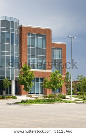 A modern office building in blue glass and red brick, with an empty parking lot in the foreground. - stock photo
