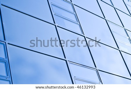 A modern office building made of glass, blue professional hue - stock photo