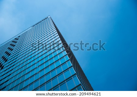 A modern office building with clear blue sky. - stock photo