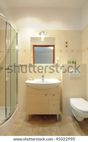 A modern sink on the wooden cupboard in a tiled bathroom underneath a mirror. - stock photo