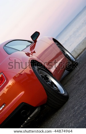 A modern sports car parked at the beach around sunset. - stock photo