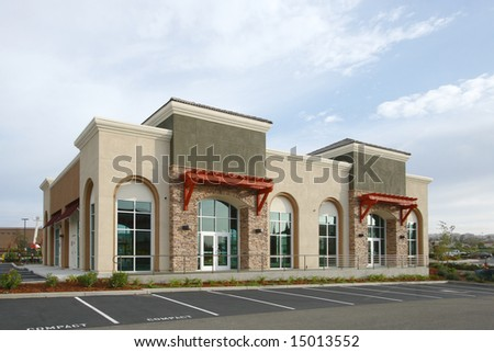 A modern strip mall with the sun setting - stock photo