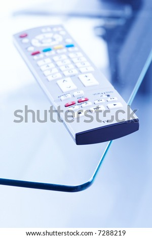 a modern tv and audio remote control is lying on a glass table ( focus on front part only, small focus area, small depth of field) - stock photo