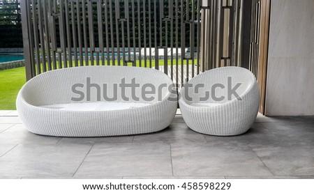 A modern white wicker garden sofa or love seat in the home garden. - stock photo