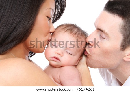 A mom and dad parent kissing their young baby - stock photo