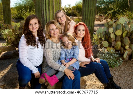 A mom and her four daughters pose for a portrait in the Arizona desert.  All the girls look different and yet alike.  They are close and happy. - stock photo