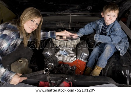 A mom and son hanging out working on a car's engine together with smiles on their faces.