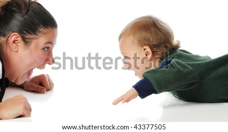 A mom and toddler playing silly face games on the floor.  Isolated on white. - stock photo