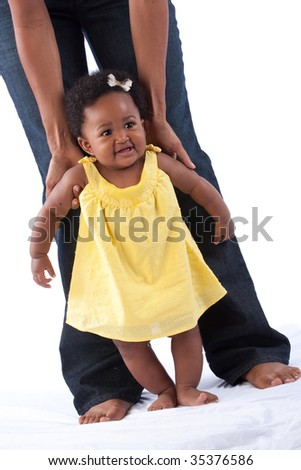 a mom helps her baby daughter take her first steps - foreground muslin intentionally left in - stock photo