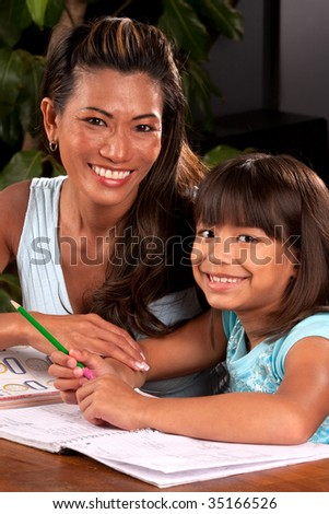a mom helps her daughter with homework - stock photo