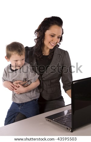 A mom holding her son while trying to work on her computer, with a smile on her face.