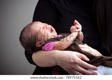 A mom holds a young newborn baby girl in her arms that is upset and crying. - stock photo