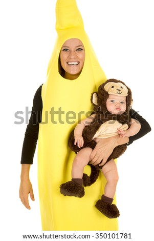 a mom in her banana costume with a smile, holding on to her little baby in her monkey costume.