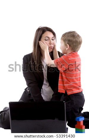 A mom is trying to look at her computer while her son tries to get her attention.
