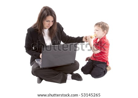 A mom is trying to work while feed her son. - stock photo