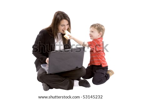 A mom is working on her computer while her son gives her a bite of his sandwich - stock photo