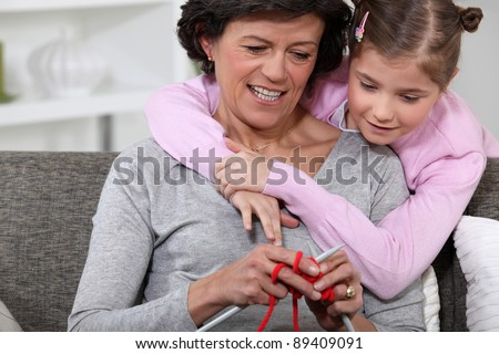 A mom showing how to knit to her daughter. - stock photo