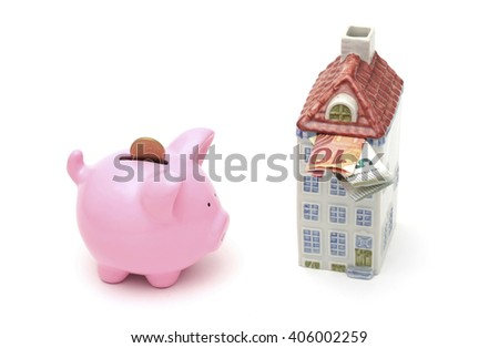 A money box in the shape of a house filled with money next to a piggy bank  - stock photo