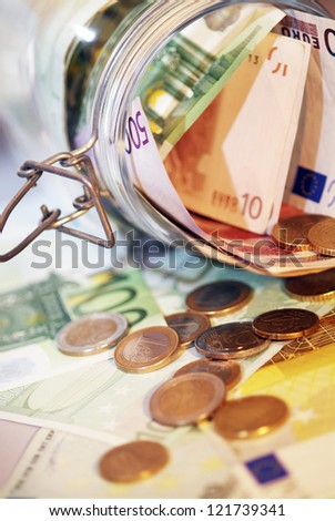 A Money jar full of money .Shallow focus. - stock photo