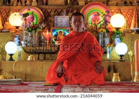 A monk meditating in the lotus position in front of golden Buddhas - stock photo