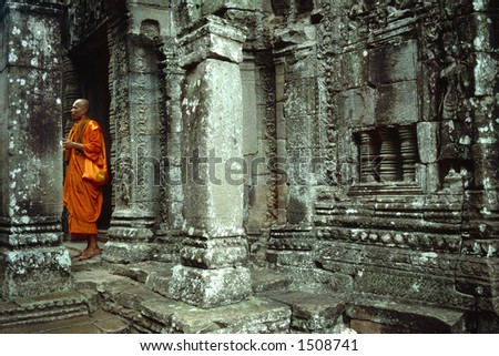 A monk seeks spiritual guidance in the magnificent Bayon Temple of Angkor Wat, Cambodia. - stock photo