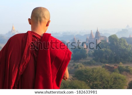 A monk standing in front of vast of temples valley in ancient Bagan city, Mandalay region, Myanmar - stock photo