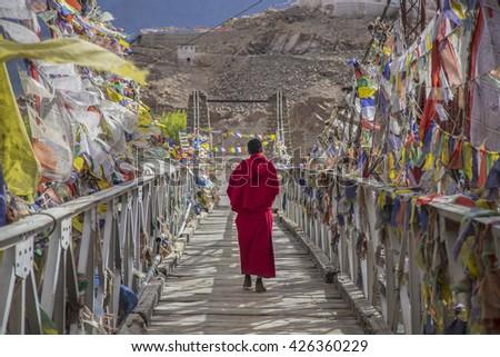 A monk walks onthe bridge pathway surrounded by colorful tibetan prayer flags , Ladakh , India  - stock photo
