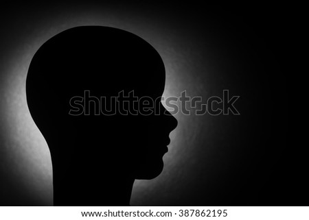 A monochromatic silhouetted side profile of a female mannequin head again a black background