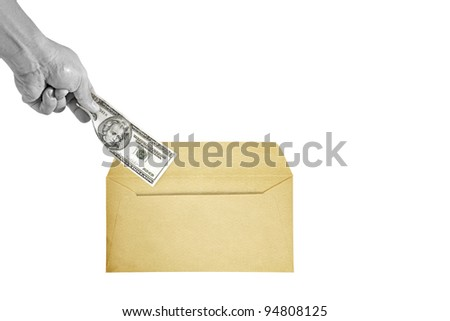 A monochrome hand inserting a twenty US dollar currency bill into a brown paper envelope, isolated against white. - stock photo