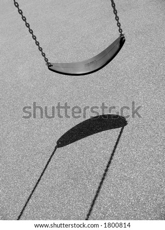 A monochrome shot of an empty swing at a playground with harsh lighting and distinct shadow. - stock photo