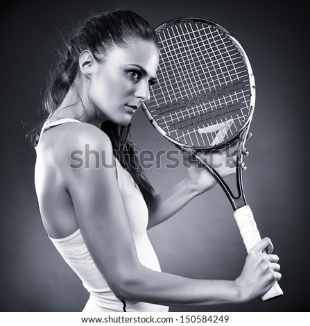 A monochrome studio shot of a young female tennis player holding the racket - stock photo