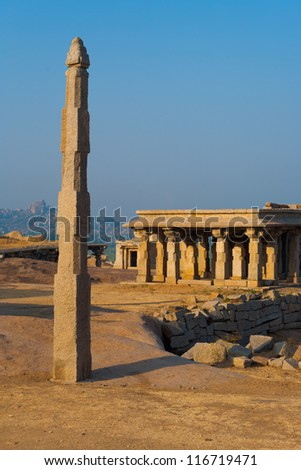 A monolithic free standing stone column stands atop a hill among the ancient ruins of Hampi, Karnataka, India - stock photo