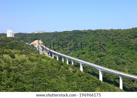 A monorail track cuts through a dense forest. - stock photo