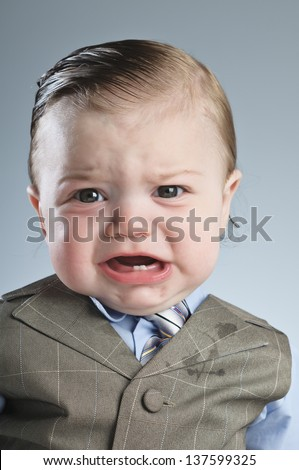 A 7 month old baby dressed in a suit.
