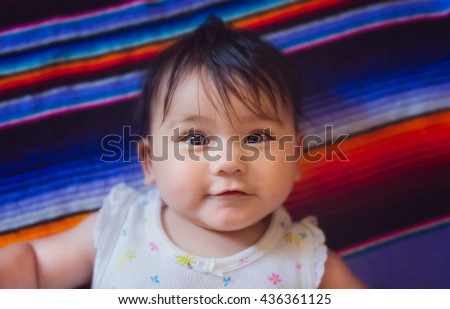 A 5 month old baby girl laying on a mexican blanket.  - stock photo