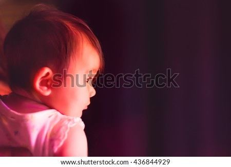 A 5 month old baby watching a dance show from back stage.  - stock photo