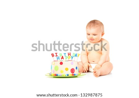 A 9 months old baby in diapers sitting next to a birthday cake isolated against white background - stock photo