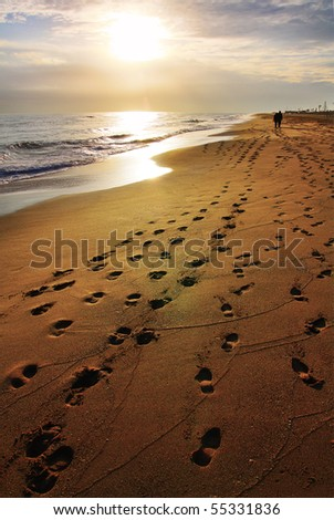 A moody, almost lonely beach - there are a lot of footprints on the sand and the sun is approaching the horizon line. - stock photo