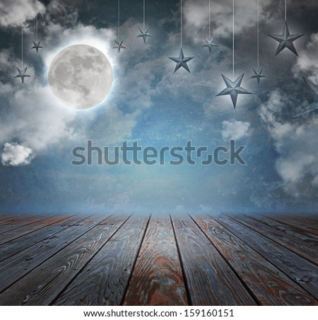 A moon and stars are in the night sky with wood on the bottom copyspace area to add your text message. - stock photo