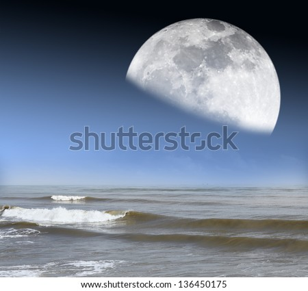 A moon rising from the horizon of an ocean with tidal waves. Elements of this image furnished by NASA. - stock photo