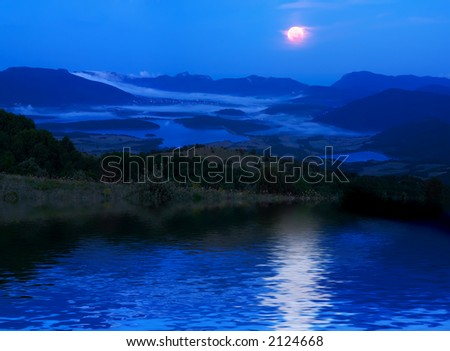 A moonlight night in mountains with reflections on water - stock photo