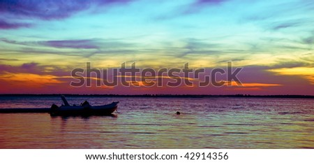 A moored little boat over the sunset background - stock photo