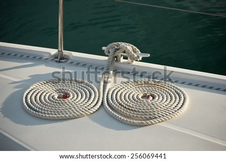A mooring ropes with a knotted ends tied around a cleat - stock photo