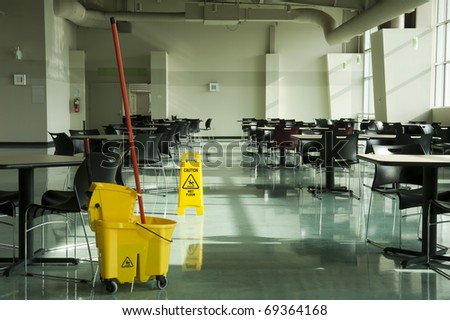 A mop, bucket and caution sign in a cafeteria environment