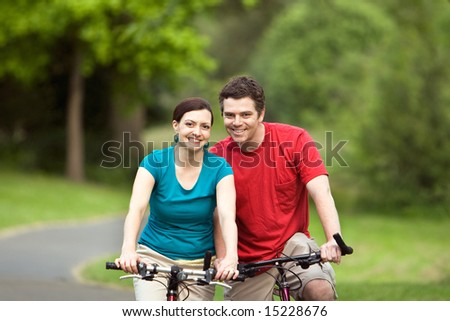 A more closer shot of a young couple, hugging and smiling at the camera and sitting on their bicycles.- horizontally framed - stock photo