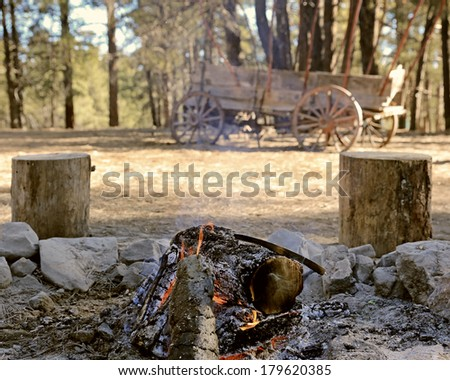 A morning campfire burns in the woods with an old frontier-style wagon in the background - stock photo