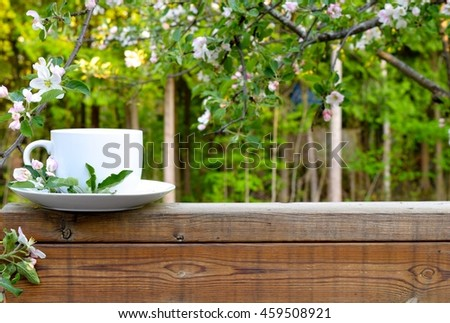 a morning cup of coffee on a wooden deck with a beautiful green background.